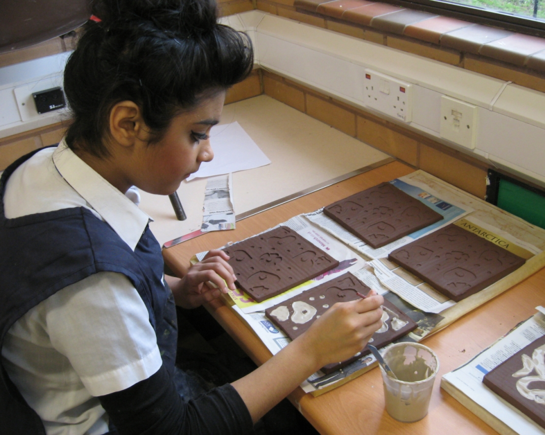 Student adds clay slip
